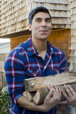 A twety-something Mexican man carries wood at a home Stock Photo - 21381972