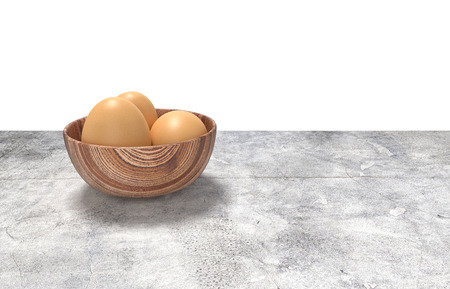Render of wooden bowl of eggs. Placed on concrete table.