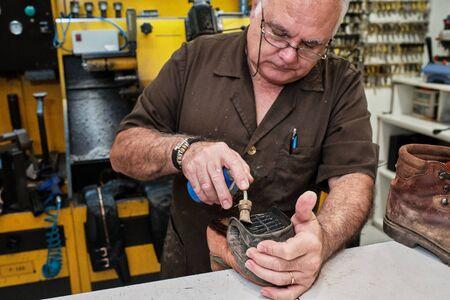 shoemaker man working in his shoe shop