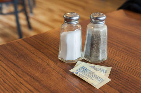 Salt and pepper sharkers and two packets of sugar substitute in a table Imagens