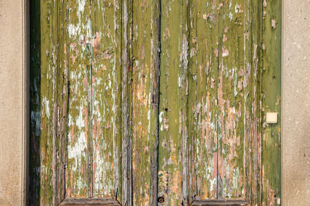 Close-up of an old door with peeled and weathered wood