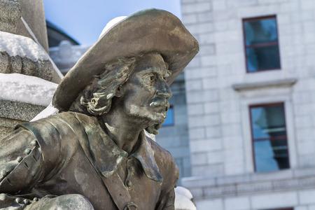 colonization: Bronze statue of men with squash hat