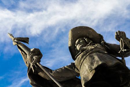 colonisation: Monumento in bronzo di uomini con lancia e spada Editoriali