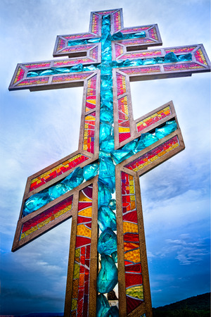 Stained glass orthodox cross on blue sunset sky closeup photo