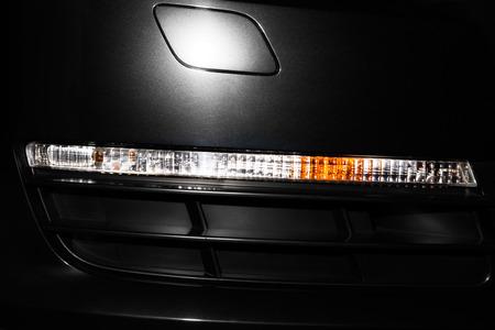 shiny black: Front turn light of black shiny sport car closeup