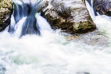 Blue waterfall in mountain closeup photo