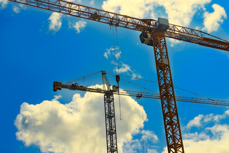 Two industrial tower cranes on blue sky with bright clouds Imagens