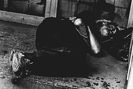 contrasty: 14-MAY-2014 Montreal,Canada-Homeless person sleeping at the Sainte Catherine street during the day in black and white