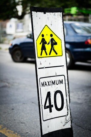 Speed limit sign at the middle of the route near school cross photo