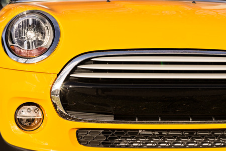 cooper: Grille bumper and headlights of yellow sport car closeup
