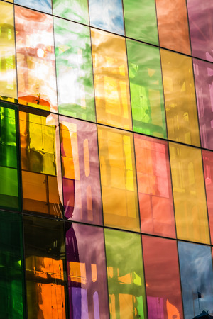 Sun and sky clouds reflections on colored stained glass of Montreal Convention Center