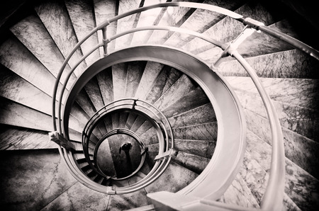 old interior: Walking woman in center of spiral stairs in black and white with light center and burned edges