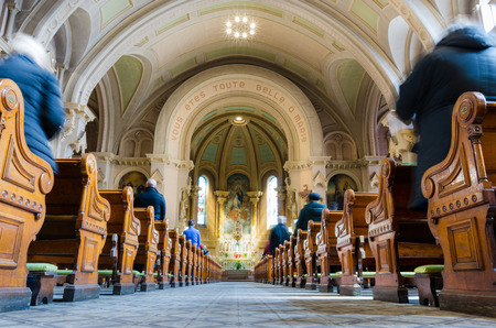 Church interior at the time of sunday mass with people and priest in Montreal Canada wide angle