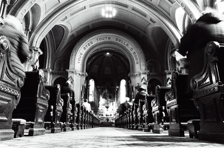 Church interior at the time of sunday mass with people and priest in Montreal Canada wide angle in black and white