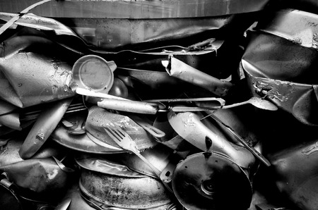 Junk pile up of old compressed ustensils and pots closeup black and white photo