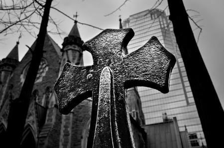 dimly: Steel religious cross in fine details on skyscraper background black and white closeup