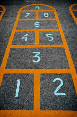 Children hopscotch game with orange borders and big light blue digits on concrete floor closeup photo