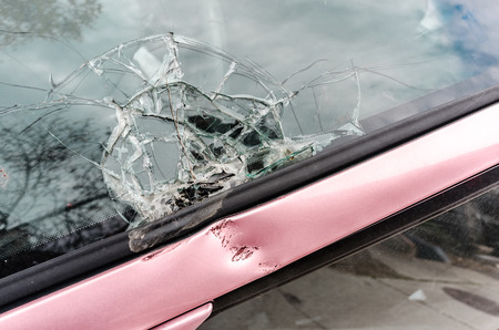 Brocken car front glass from falling tree branch closeup