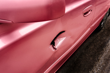 pierced: Pink car with pierced accidented door closeup Stock Photo