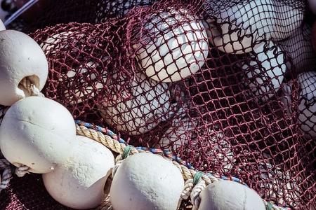 commercial fishing net: Brown fishing net with floating balls around it closeup