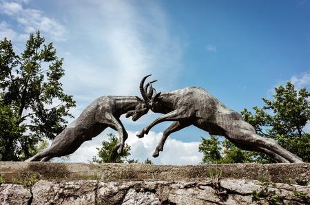 Bronze sculpture of two goats fightening on a bridge closeup