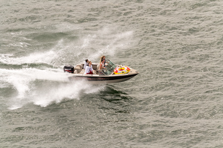 laurent: Montreal, Canada - June 07, 2015: Four people driving a speed boat in Saint Laurent river in Montreal, Canada