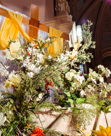 Colorful flowers over Christ cross in catholic church mass closeup Stock Photo