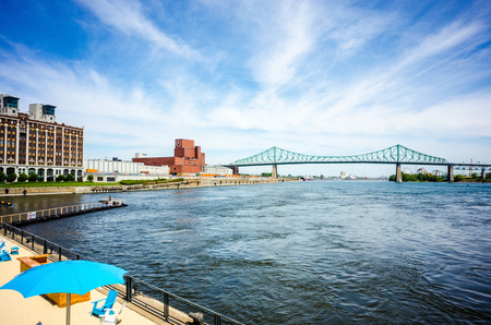 laurent: Blue sky over Montreal old port beach on Saint Laurent river facing Jack Cartier bridge Editorial