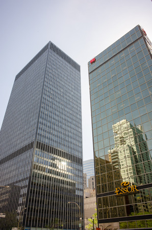 kin: Montreal, Canada - June 04, 2015: Kin EssorNational Bank and Bank of Montreal skyscrapers facade reflections in Montreal downtown