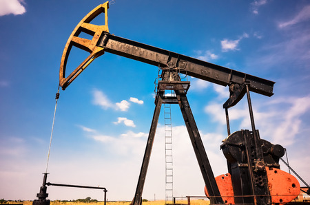 Industrial pump jack at oil and gas field over blue sky with clouds in Bulgaria,Europe Stock Photo