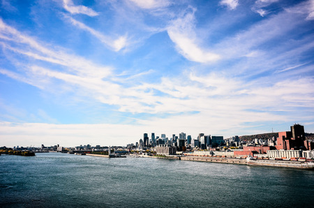 Montreal downtown and old port from St-Laurence river witn blue sky and clouds Stock Photo