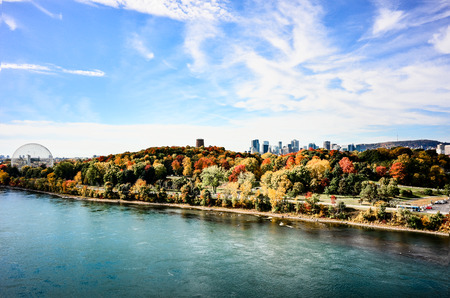 Autumn over Montreal downtown from St-Laurence river panorama with blue sky and water