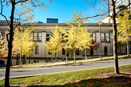Men walking in front of UQAM university building between trees in autumn colors