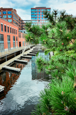 Water channels with boat docks in Montreal old industrial district to attract new customers and comply with new environment plan