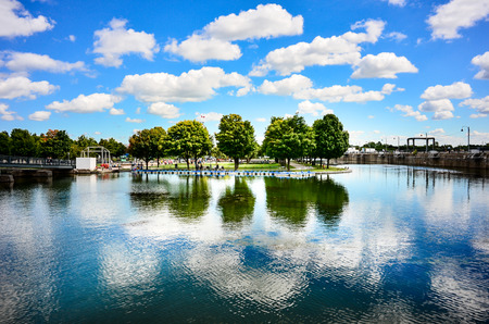 Artificial isle trees ,sky and clouds reflection at Montreal Old Port panorama