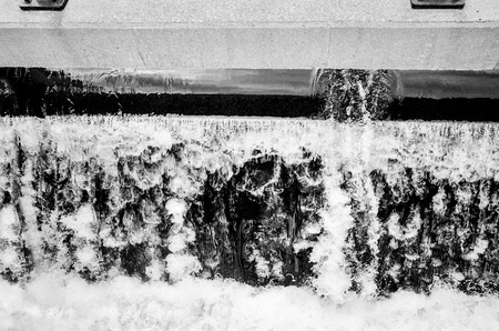 Small waterfall at Montreal downtown water channels in black and white closeup