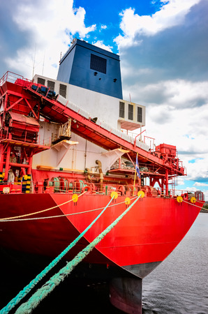 Montreal old port red transportation ship docked with ropes on blue sky with clouds background Stock Photo