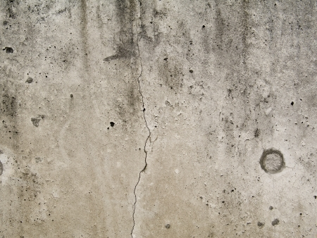 Textured concrete wall with holes and cracks