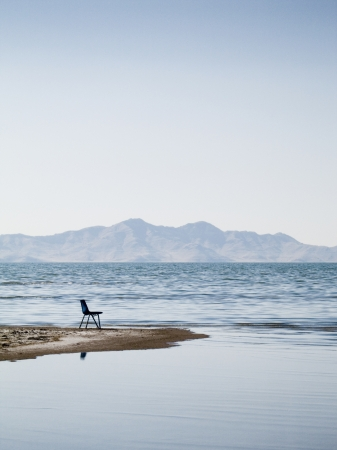 A lone empty chair on the edge of the Great Salt Lake shoreline with Antelope Island State Park in the distance