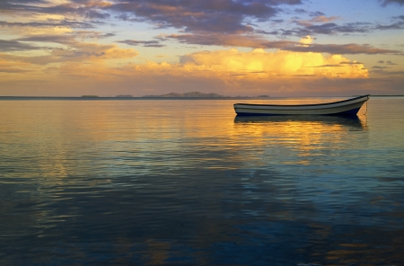 A lone fishing boat on the ocean at sunset just off of Fiji  Stock fotó