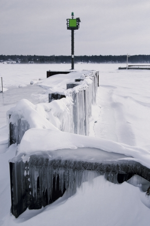 Photo take on Madeline Island of the Apostle Islands in Wisconsin on Lake Superior with extreme ice covered pier and sheets of snow over the great lake Stock fotó