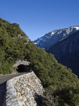 Roadway tunnel to Yosemite National Park with snow covered mountains in background and people walking on roadway