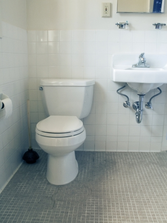 Small bathroom with white old white tiles with toilet and sink