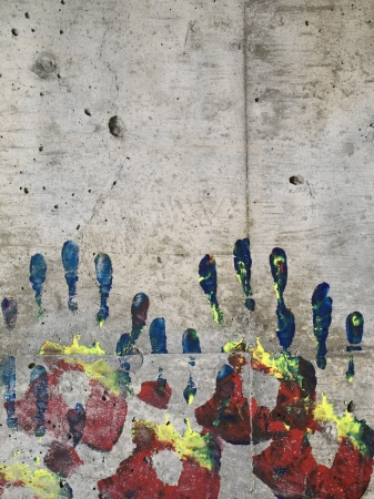 Painted handprints on concrete wall