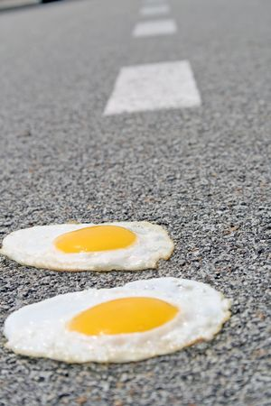 fried eggs on a hot street in the summer Фото со стока