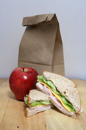 a brown bag lunch with an apple, sandwich and brown bag Banco de Imagens