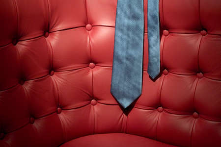 professionalism: Blue tie on red leather couch Stock Photo
