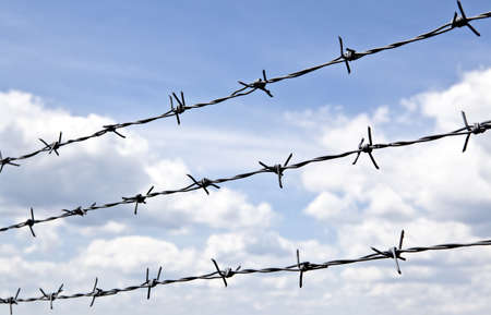 Barbed wire against blue sky with clouds Stock Photo - 14408063