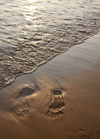 Footsteps in sand at sundown photo
