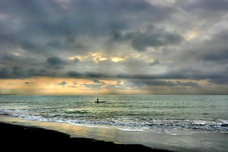 Man with canoe on the Pacific Ocean.